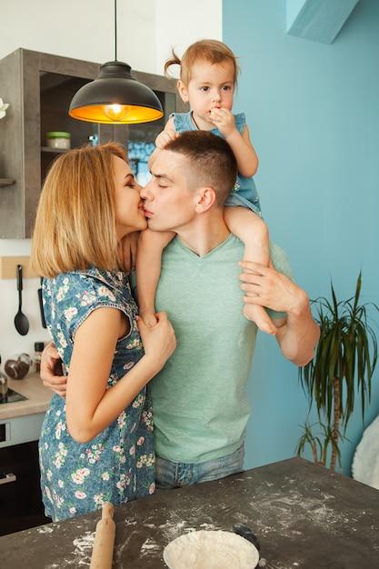 キッチンの準備で幸せな笑みを浮かべて白人家族 Premium写真