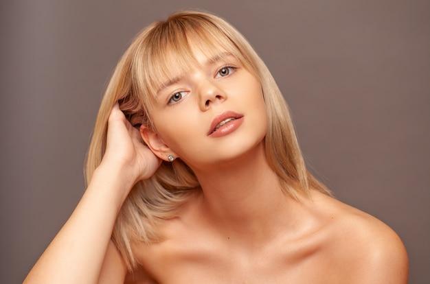 新鮮な健康的な肌と彼女の顔に触れる毛を持つ若い女性。 Premium写真
