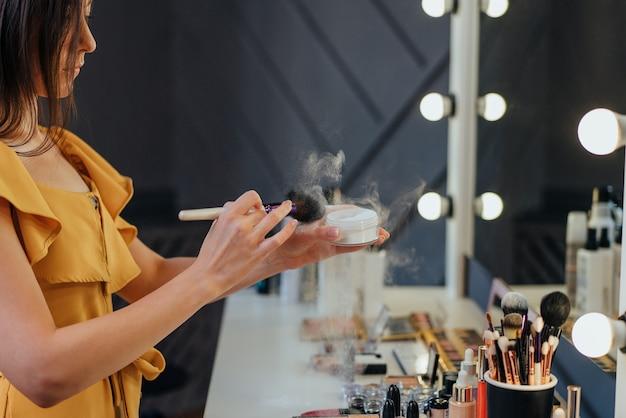 美しい若い女性は、鏡を見ながらパウダーを使用して化粧をしています。 Premium写真