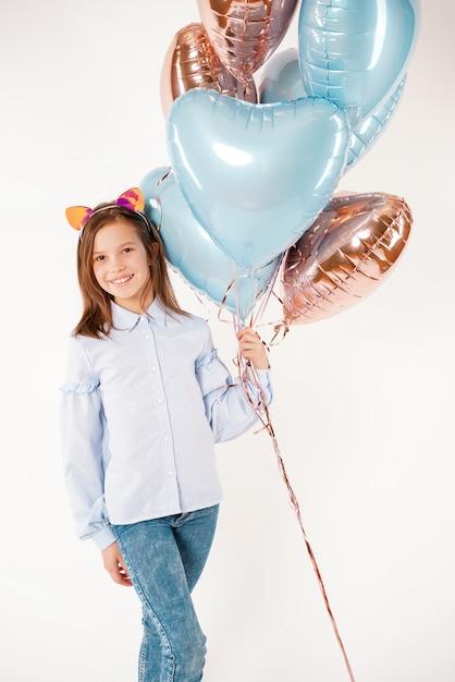 Смешная девчонка с кошачьими ушами, держа воздушные шары. концепт дня рождения Premium Фотографии