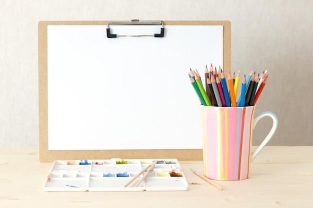 ドローイングボードと文房具オブジェクトの芸術家の机。スタジオは木製の背景で撮影しました。 Premium写真