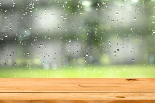 ウィンドウガーデンの背景に水滴の上の空の木製テーブル Premium写真