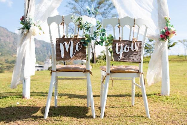 私とあなたの結婚式は、森の中に立っている椅子に署名します。 Premium写真