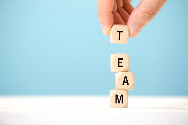 手はチームを表す木製のテーブルの上の手紙と木製キューブ要素を保持します。事業コンセプト Premium写真