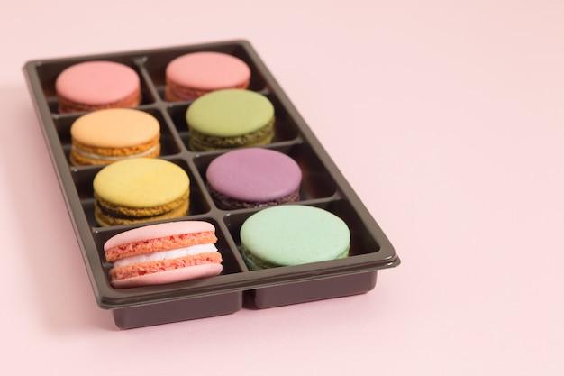 Сладкие и красочные французские миндальное печенье или макарон на розовом фоне, десерт. Premium Фотографии