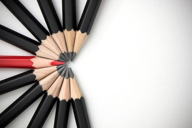 赤鉛筆は白いテーブルにたくさんの同一の黒い仲間の群れから目立ちます。 Premium写真