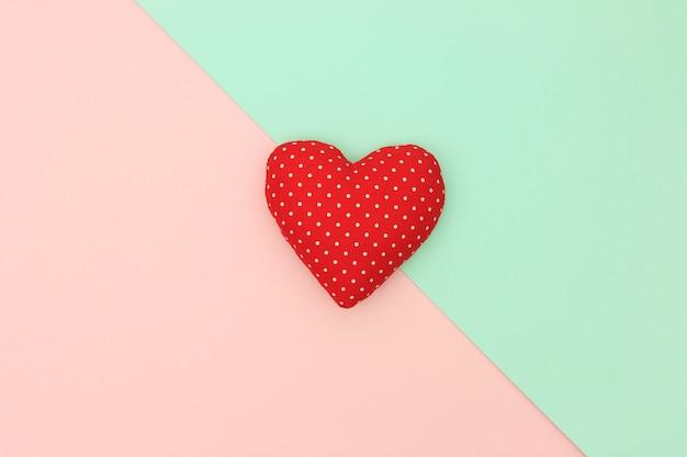 パステル調の背景にコピースペースと赤いハート。愛とバレンタインの日の概念。最小限のスタイル Premium写真