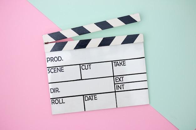 緑とピンクのペースト状の背景にクラッパーボード Premium写真