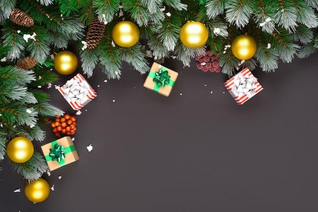 メリークリスマスまたは新年あけましておめでとうございますフレーム構成。モミの枝、クリスマスのおもちゃ、ギフトボックス、ふわふわの雪、松ぼっくり、キャンディ、黒い背景に冬の果実。フラットレイアウト、テキストのコピースペース。 Premium写真