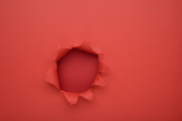 引き裂かれた赤い紙壁の背景。広告用のスペースをコピーして、コンテンツを提供または販売します。 Premium写真