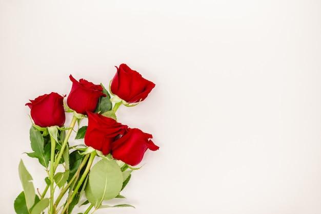 赤いリボンと赤いバラの花束。 Premium写真