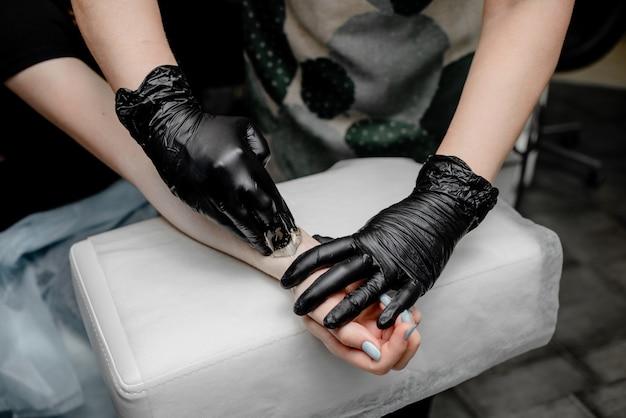 黒い手袋で脱毛するためのシュガーペーストまたはワックスハニー Premium写真