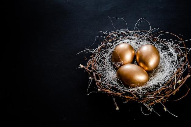 黄金のイースターエッグは黒の背景に巣します。イースターホリデー Premium写真