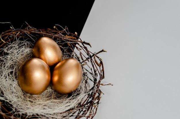 黒と白の抽象的な背景に巣の中の黄金の卵。 Premium写真