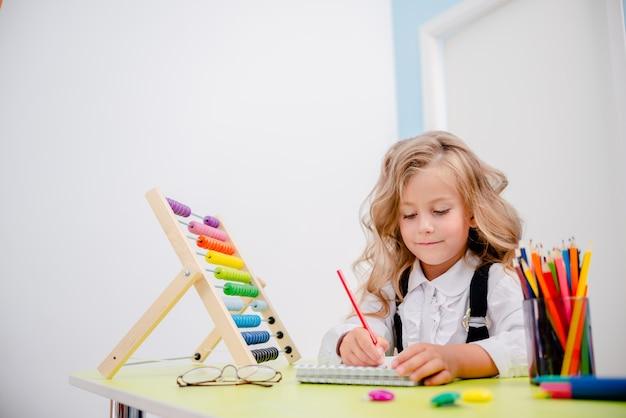 Вдохновленный маленькая девочка за столом с карандашами. парта со школьными принадлежностями, карандашами, сумками, бумажниками и счетами. стекла маленькой белокурой девушки нося назад к концепции школы. Premium Фотографии