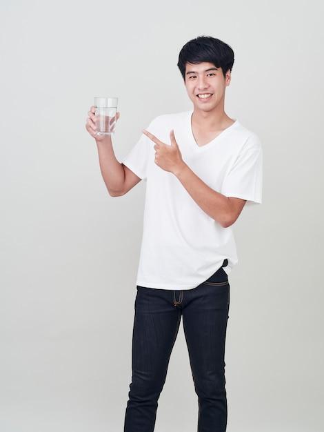 水のガラスを保持している若い笑みを浮かべて男 Premium写真