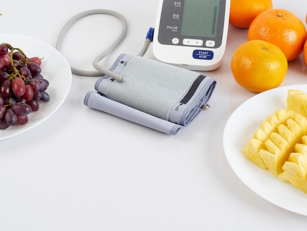 Монитор артериального давления и фрукты Premium Фотографии