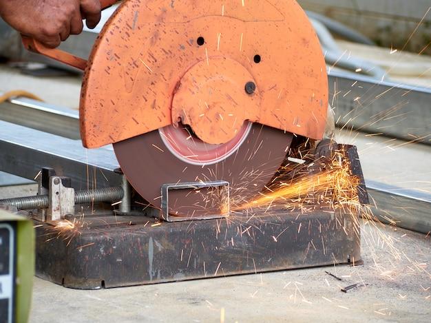 Рабочий режет железо с помощью отрезных кругов. Premium Фотографии