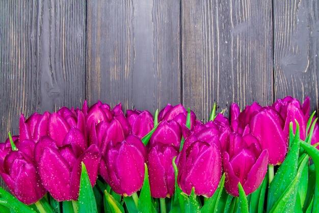黒い木製の背景、テクスチャに明るいピンクのチューリップと女性の日コピースペース Premium写真