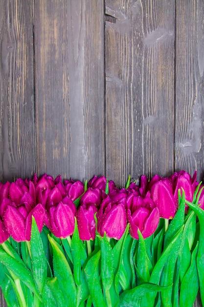 黒の木製の背景に明るいピンクのチューリップと女性の日の垂直コピースペース Premium写真