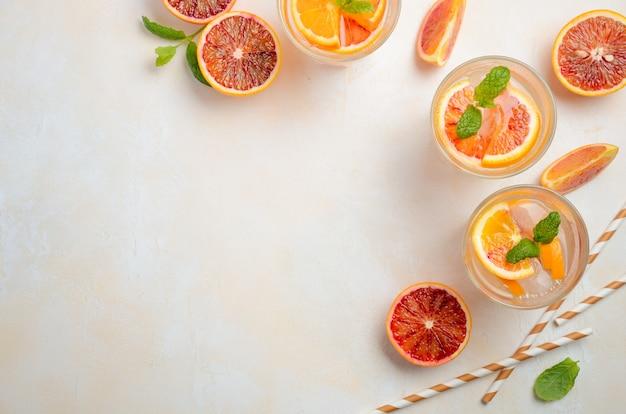 Холодный освежающий напиток с кусочками апельсина в стакане на белом бетонном фоне Premium Фотографии