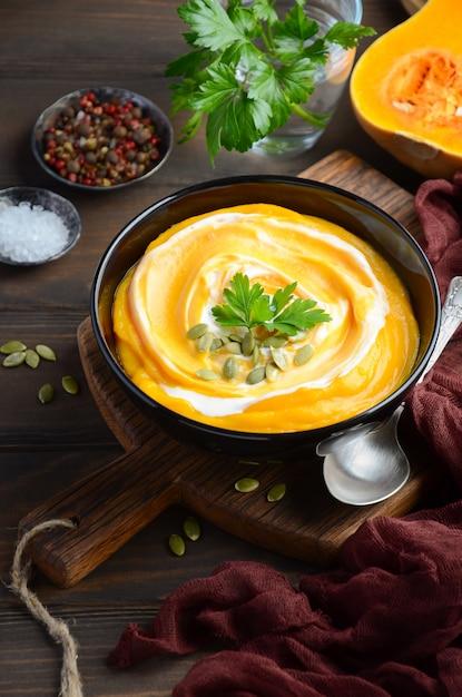 木製のテーブルにクリームとカボチャの種のカボチャのクリームスープ。 Premium写真