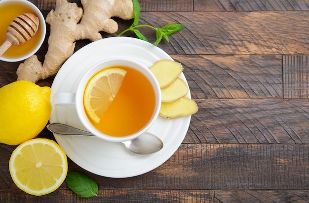レモンと蜂蜜、木製テーブル、トップビュー、コピースペースにジンジャールートティー。 Premium写真