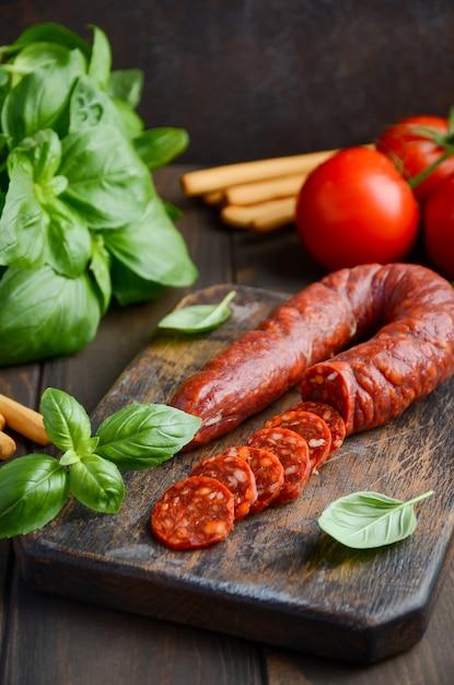 チョリソーソーセージ。スペインの伝統的なチョリソーソーセージと新鮮なハーブとトマト。 Premium写真