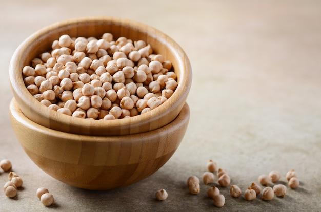 Сырцовые органические нуты в деревянном шаре, здоровый веганский вегетарианский пищевой ингредиент. Premium Фотографии