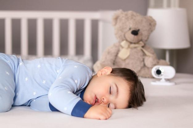 ベビーモニター付きのベッドで静かに眠っている水色のパジャマでかわいい男の子 Premium写真