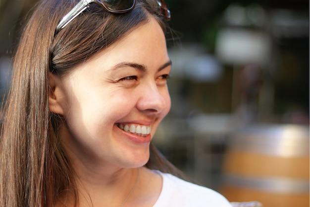 長い茶色の髪、自然の美しさ、化粧なしで美しい笑顔幸せな女。 Premium写真