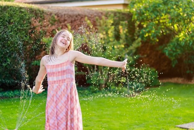 水の下で夏の庭で楽しく笑って幸せなプレティーンの女の子は、散水管からスプレーを削除します。 Premium写真