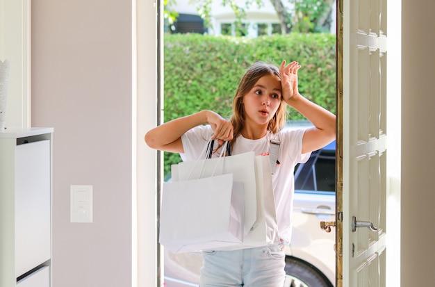 美しい若い女の子が彼女の手の中にショッピングバッグを持って帰って家に帰って疲れた Premium写真