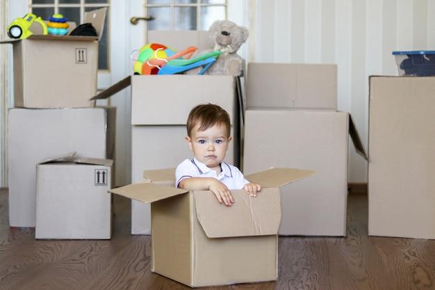 バックグラウンドのおもちゃでいっぱいの大きな箱で段ボール箱の中に座っているかわいい小さな赤ちゃん Premium写真