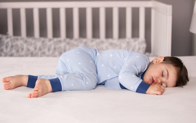 自宅のベッドで安らかに眠っている水色のパジャマでかわいい男の子。 Premium写真
