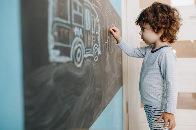Кудрявый маленький мальчик рисует мелом на доске в своей комнате Premium Фотографии