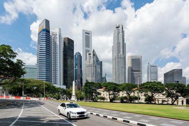 Такси управляя в дороге в сингапуре городском с небоскребами сингапура строя в предпосылке. азии. Premium Фотографии