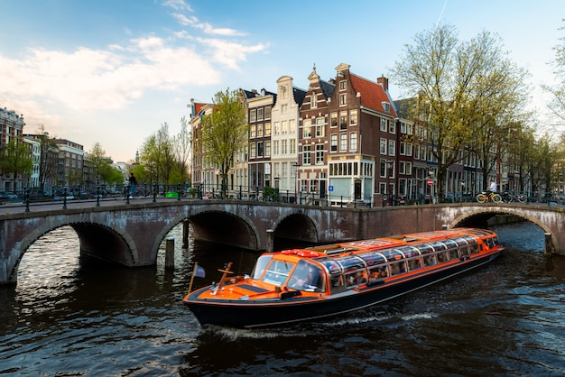 オランダ、アムステルダムのオランダの伝統的な家とアムステルダムの運河クルーズ船。 Premium写真