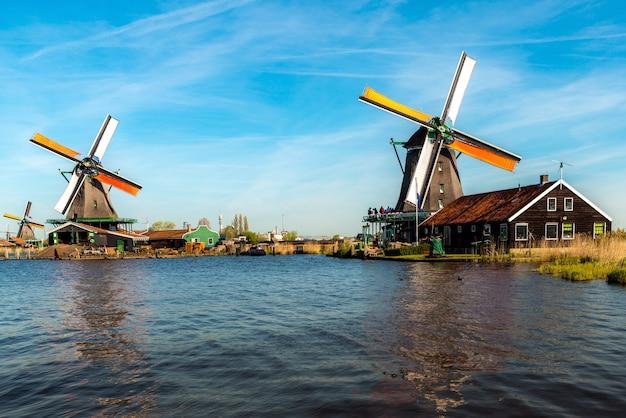 ザーンセスカンス、オランダのザーン川のそばにある伝統的なオランダ風車。 Premium写真