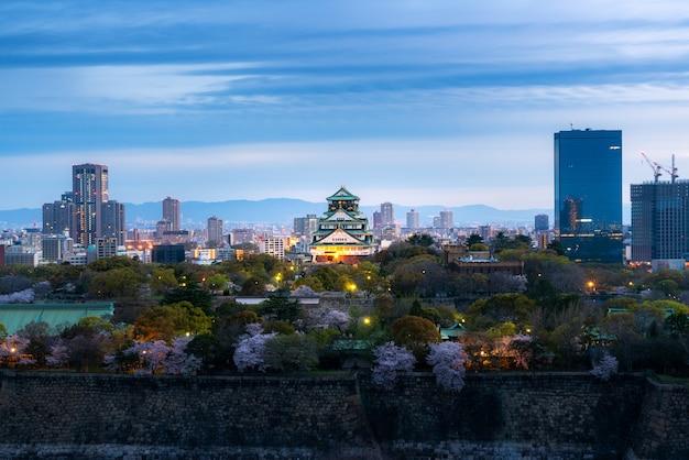 日本の大阪の桜とビジネス地区のある大阪城。 Premium写真