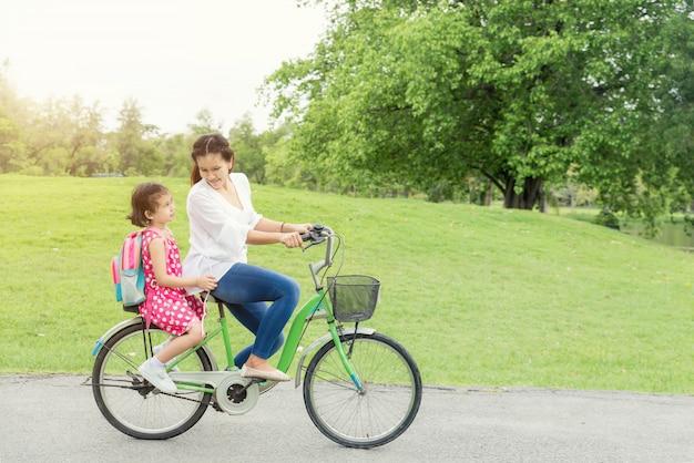 母と娘が一緒に自転車をサイクリングします。 Premium写真