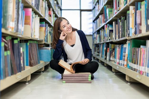 アジアの学生が大学の図書館で読書しています。 Premium写真