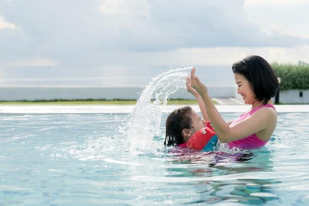 Счастливая азиатская мать и дочь веселятся в бассейне отеля Premium Фотографии