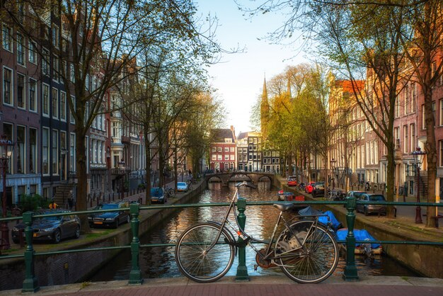 オランダの伝統的な家屋とアムステルダム、オランダのアムステルダムの運河と橋の上の自転車。 Premium写真