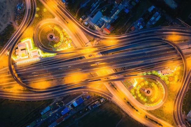 高速道路ジャンクションの空撮夜、タイのバンコク、都市の平面図。道路のジャンクション、交通の概要、交通機関の概念を横断する光の道。 Premium写真