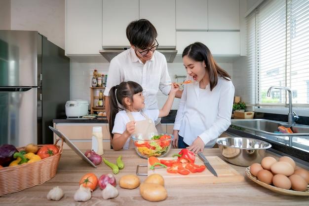 Азиатские дочери кормят салат своей мамой и папой, когда семья готовит на кухне дома. семейная жизнь, любовные отношения или концепция развлечений на дому Premium Фотографии