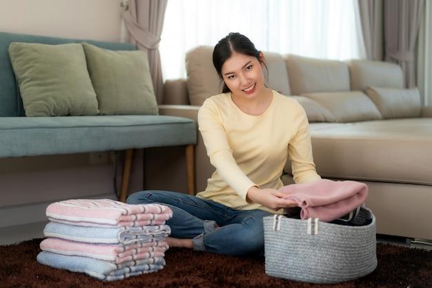 Усмехаясь азиатская женщина держа чистые сложенные одежды дома. довольно молодая леди, сидя на полу с диваном. концепция прачечной и бытовой. передний план. Premium Фотографии