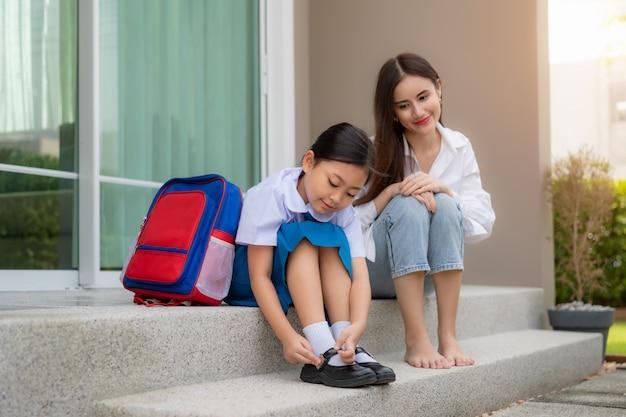 制服を着た娘の就学前の生徒が自分の靴を履いているのを見ているアジアの母。 Premium写真