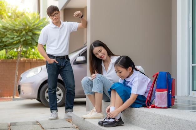 アジアの家族の父親、母親の娘の就学前の制服を着て自分の靴を履いている Premium写真