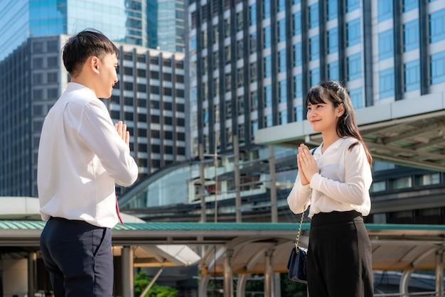 Два азиатских молодых бизнесмена и деловые друзья встречаются в шрифте офисного здания вместо того, чтобы приветствовать их объятиями или рукопожатием, они вместо этого уважают. Premium Фотографии